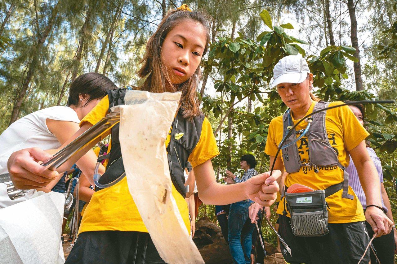 泰國十二歲環保少女黎利(中)在曼谷清理塑膠垃圾。 (法新社)