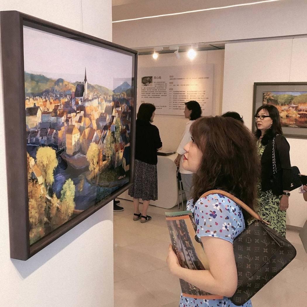 《駐足X神往》畫展中,參觀來賓凝神欣賞孫心皓最有感的幅畫作之一《千年小鎮》。項家...