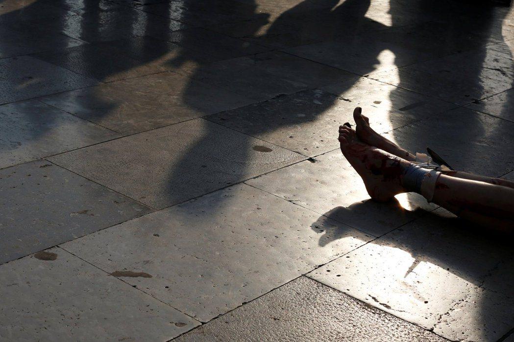 示威者在身上綑綁膠帶並塗上紅色顏料,抗議針對婦女的暴力行為。攝於2017年2月2...