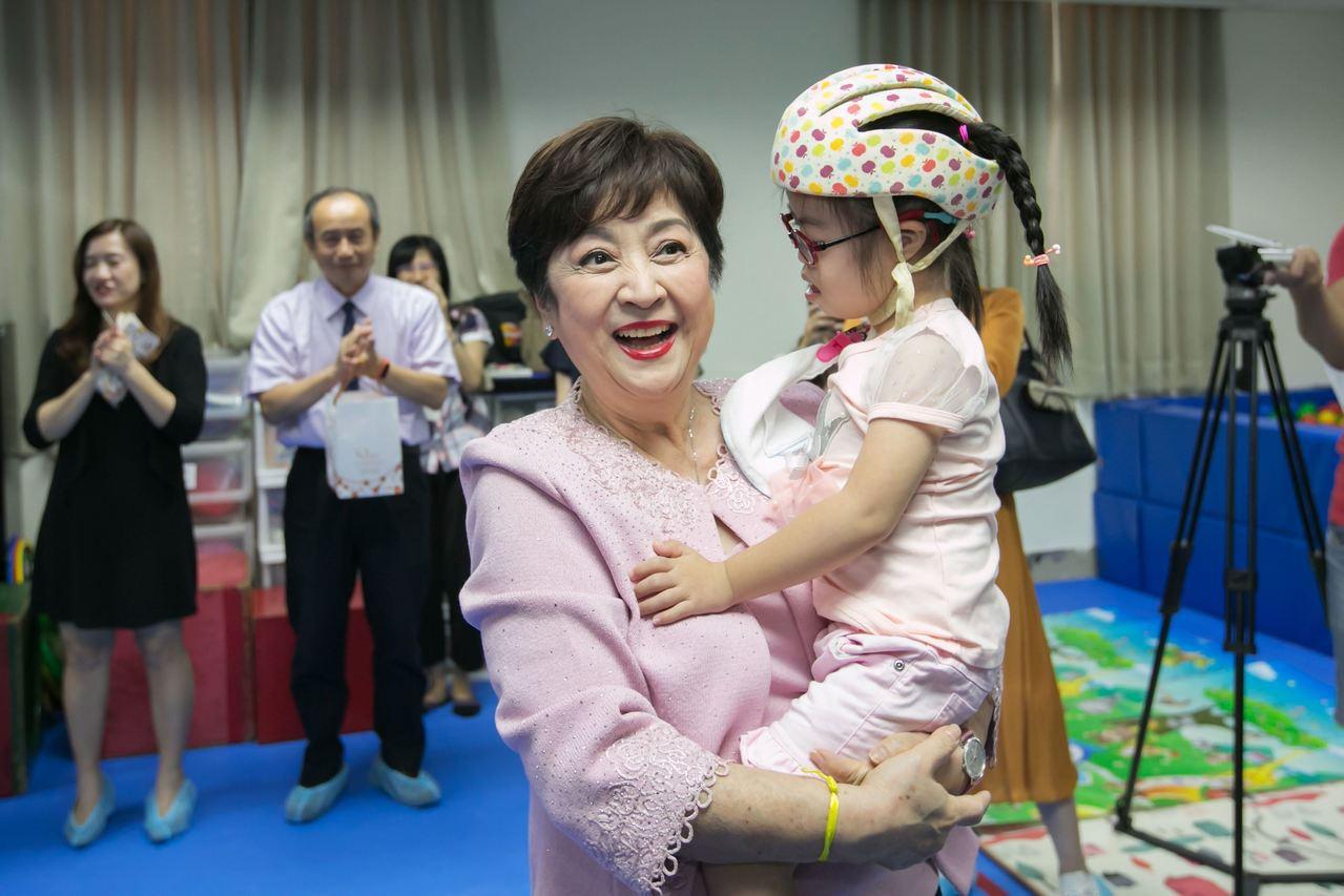 高雄公益大使甄珍到早療中心開心抱著慢飛兒。圖/高雄市政府新聞局提供