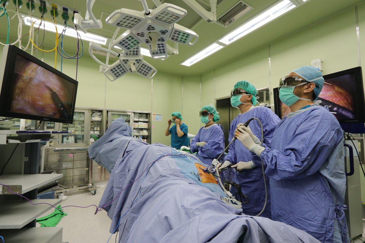 亞洲大學附屬醫院大腸直腸外科主任江驊哲(右二)和醫療團隊以3D立體腹腔鏡手術切除...
