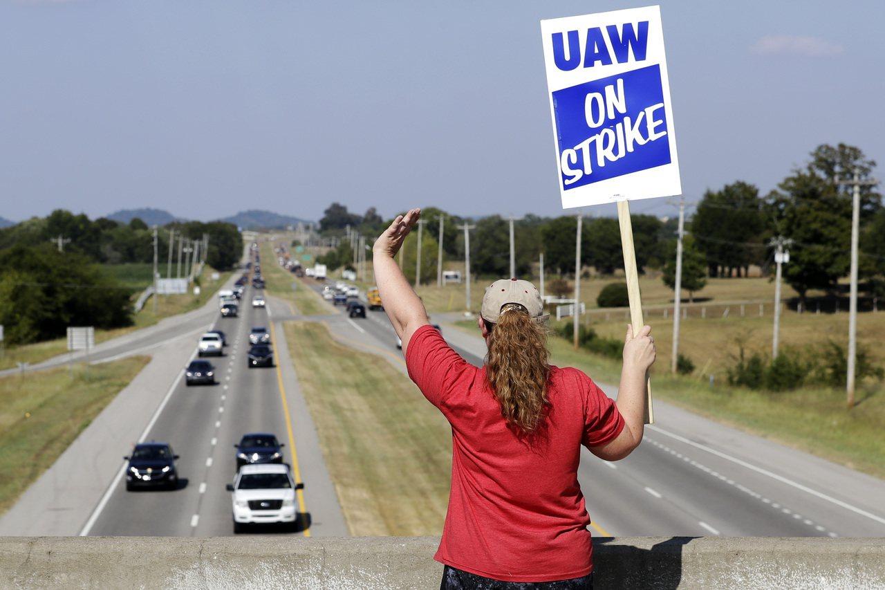 美國通用汽車公司田納西州車廠一名員工,16日在馬路的天橋上舉起罷工糾察隊的牌子。...