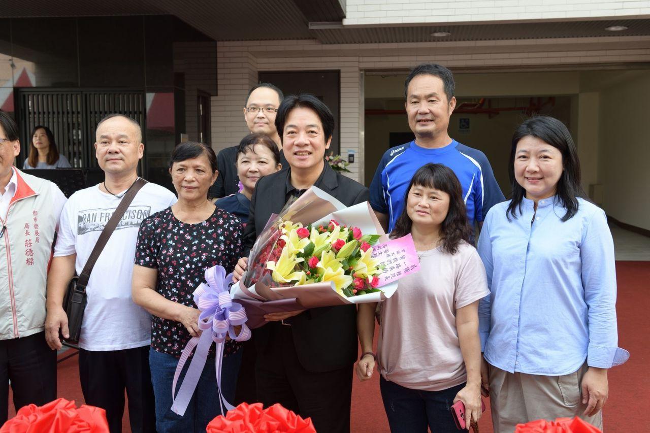 台南震災重建公寓大樓落成,賴神提前到場低調祝福住戶,住戶獻花感謝。圖/讀者提供