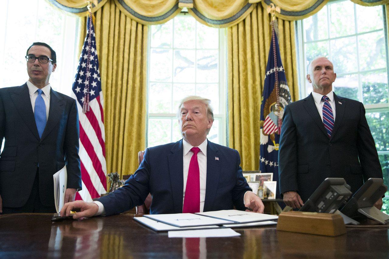 川普今年6月24日簽署制裁伊朗的行政命令時,財長米努勤(左)與副總統潘斯(右)在...