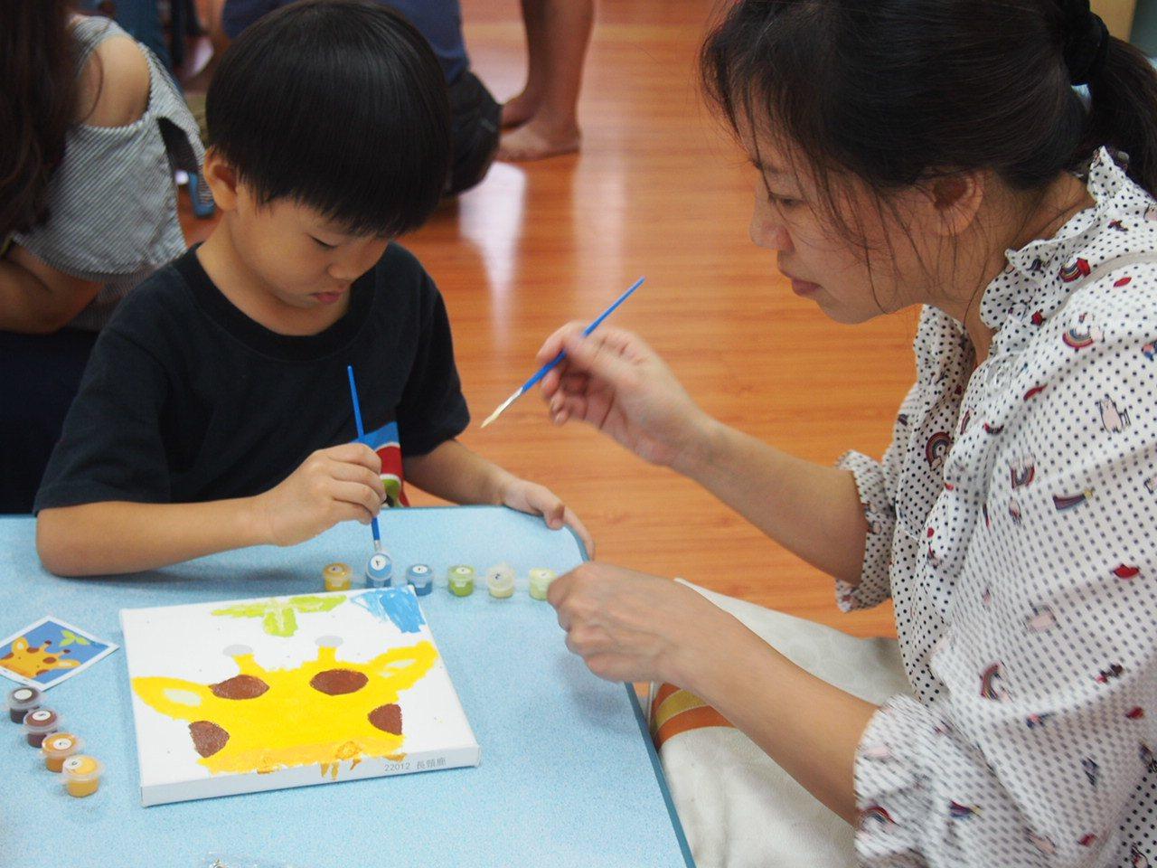 為降低孩童開學不安,慈文國小安排幼兒園的孩童,和家長一起用襪子製成娃娃及畫圖,將...