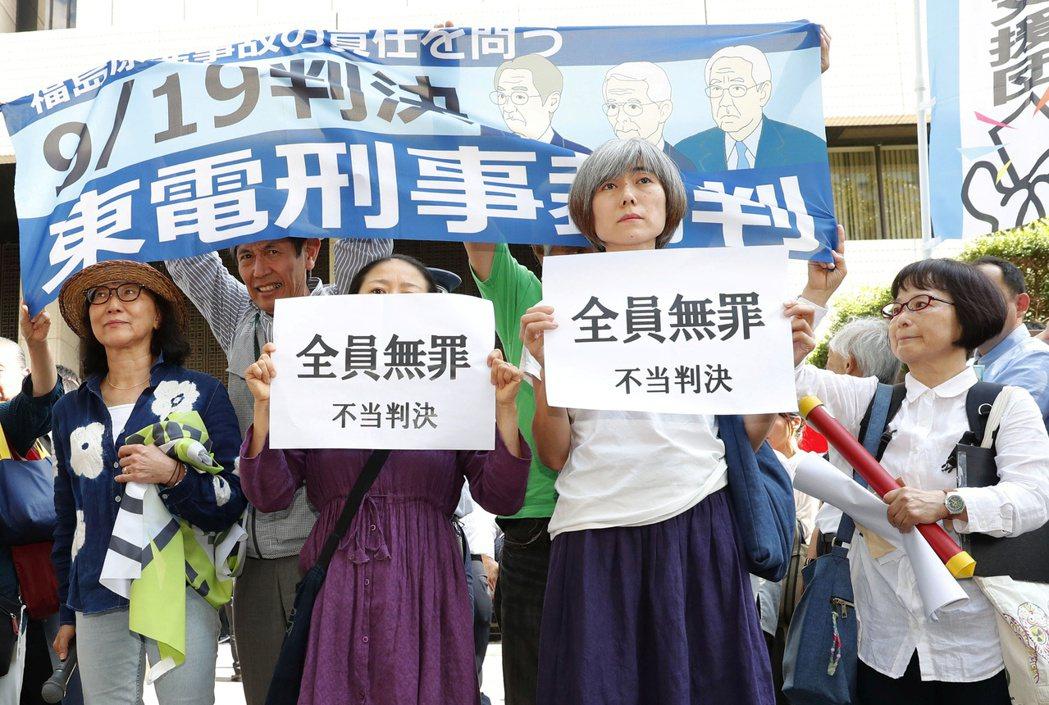 示威人士19日在法院外舉標語抗議審判不公,東電前高層才會全部無罪。路透