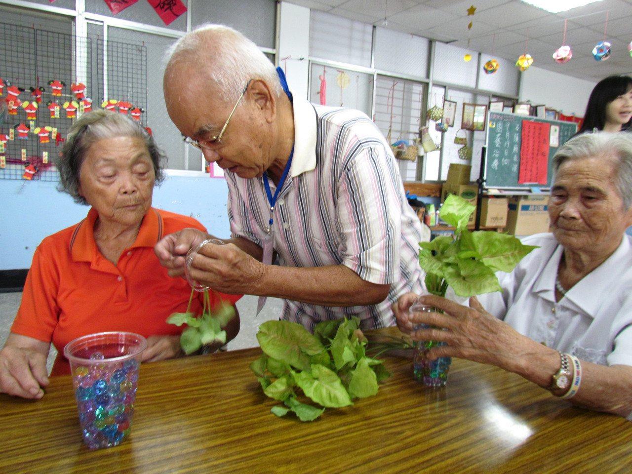 77歲學員蔡重信(中)退休後每天種菜過著田園生活,此次擔任助教教長輩們製作盆栽,...