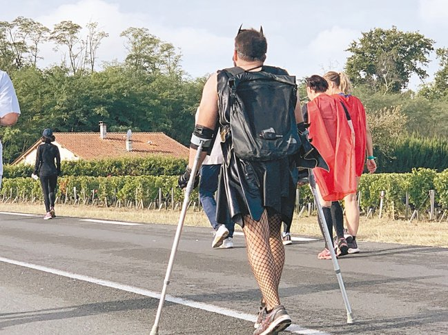 有身障人士扮成蝙蝠俠、拄著枴杖參賽,背影令人動容。 圖/陳志光、游慧君