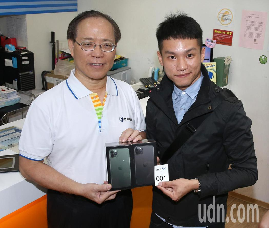 中華電信董事長謝繼茂(左)贈送手機給排隊第一名的洪先生。記者林澔一/攝影