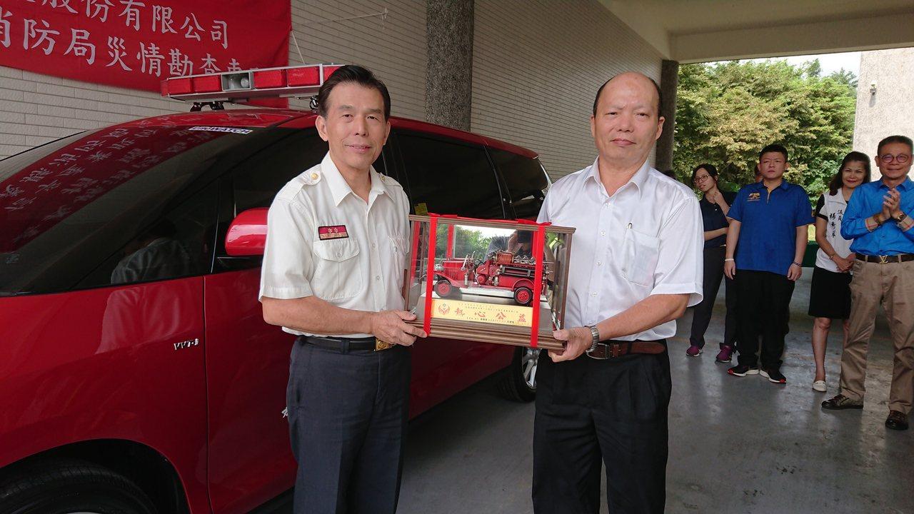 嘉義縣消防局長呂清海(左)回贈消防車模型車給信孚公司董事劉明澄。記者卜敏正/攝影
