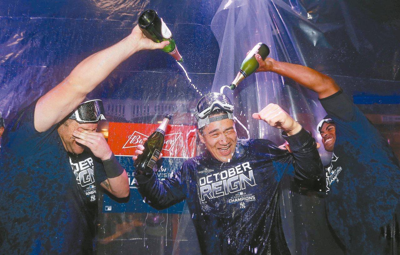 洋基隊在美聯東區封王,田中將大被隊友大淋香檳浴。 (法新社)