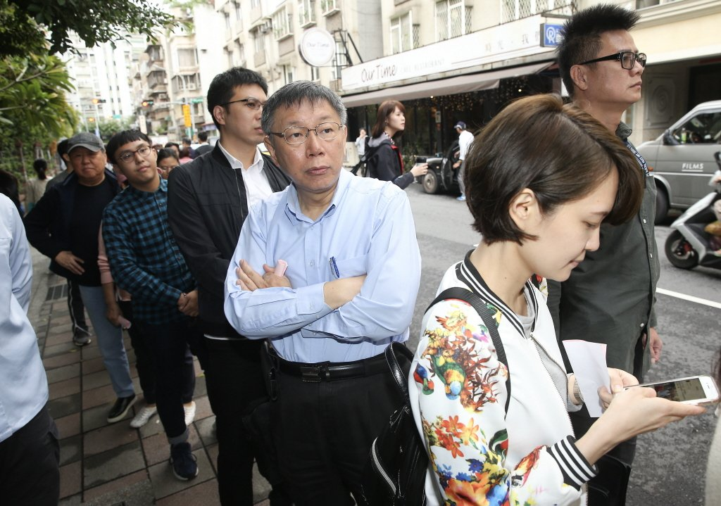 去年九合一選舉與公投,台北市長柯文哲(中)排隊投票。圖/聯合報系資料照片