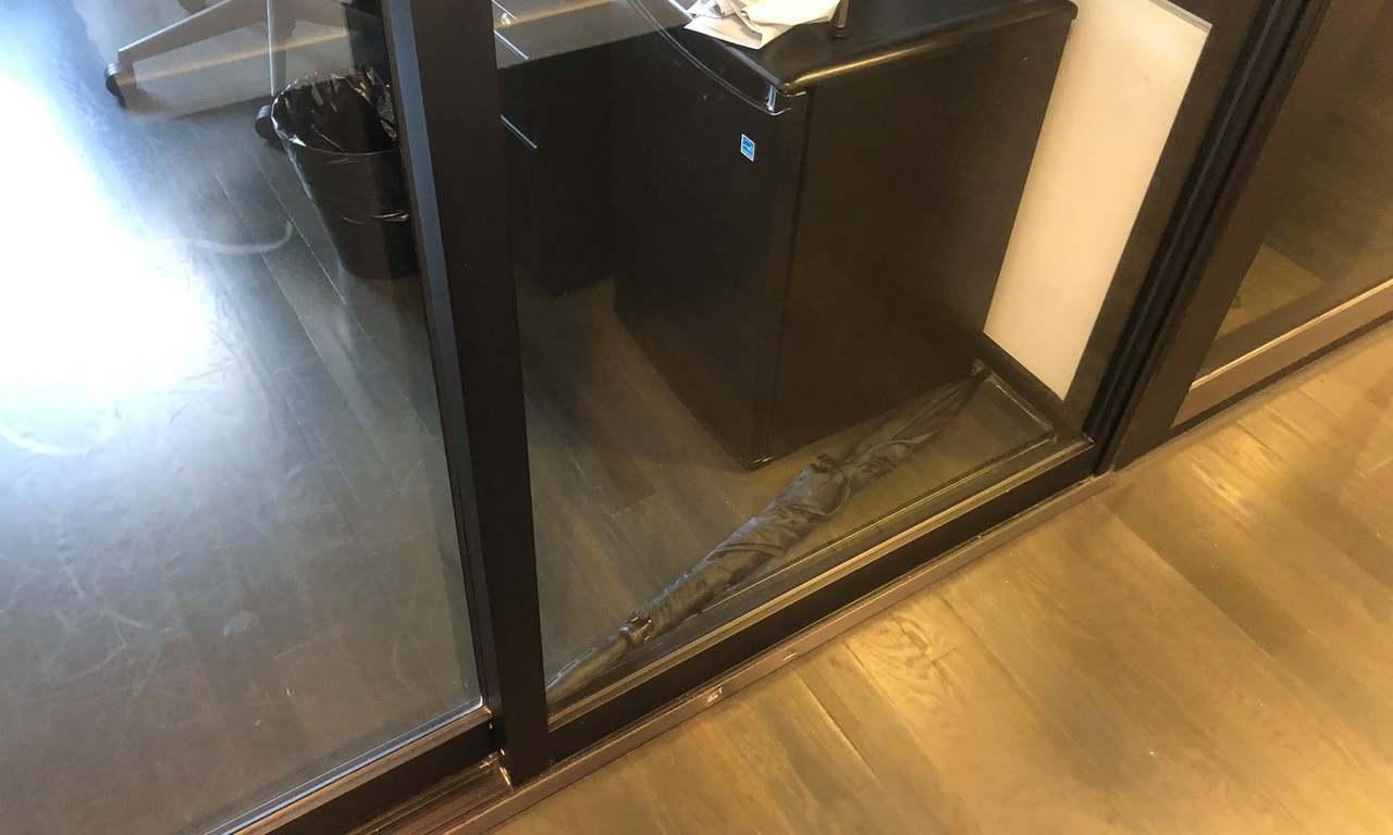 一把傘卡住玻璃門,讓辦公室員工都無法工作。圖/取自衛報