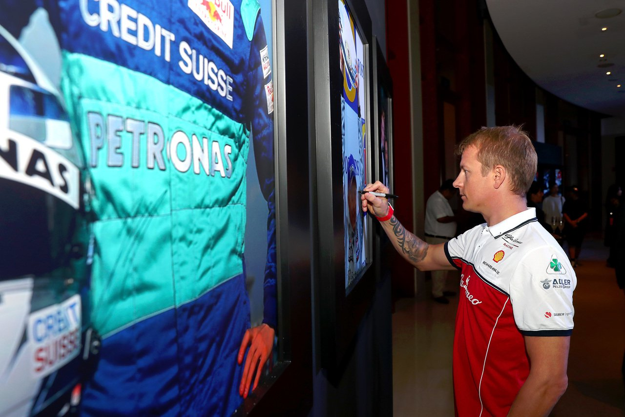 F1賽車好手Kimi Räikkönen在自己的賽車海報上,簽名留念。圖/RIC...