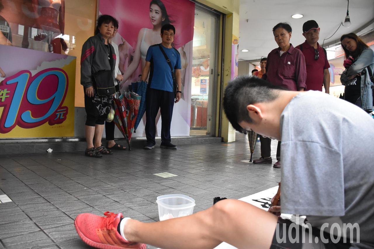 李陽在揮毫的過程中,往往讓經過的路人停下來,專心看著李陽寫毛筆字,或是拿出手機拍...