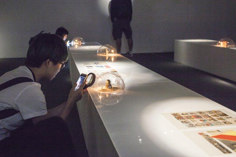 駁二將光源聚焦在原稿與袖珍模型上,讓觀展者蹲下身軀近距離觀看老吉隆坡的街景與人物。記者徐如宜/攝影