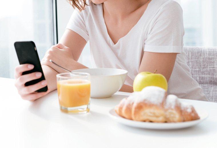 有研究指出,吃飯分心會比專心吃飯的人吃進更多熱量,腰圍恐節節失守。 圖╱123R...