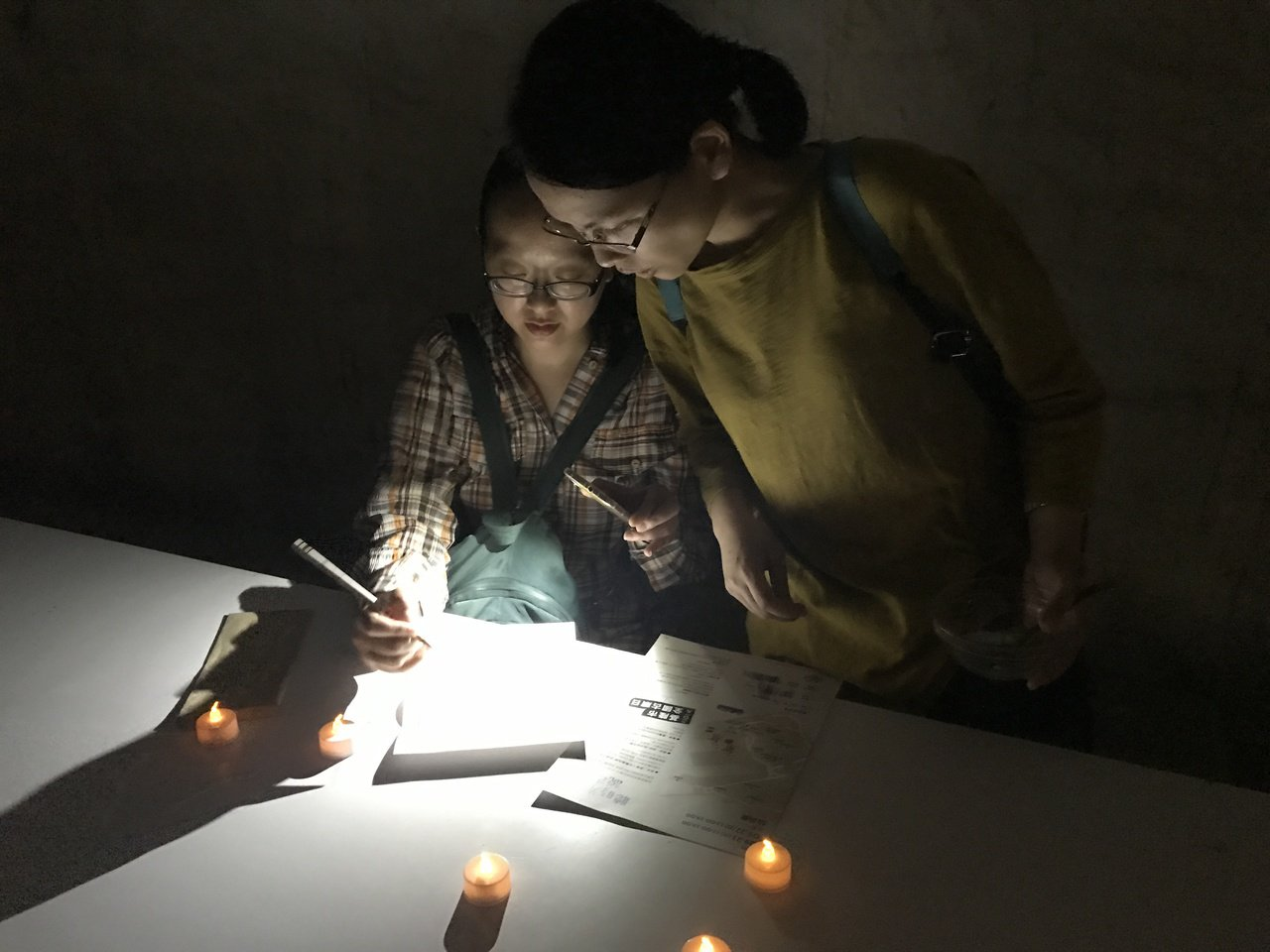 參與民眾在防空洞內就著微弱燈光寫一封信,體驗戰爭心情。記者吳淑君/攝影