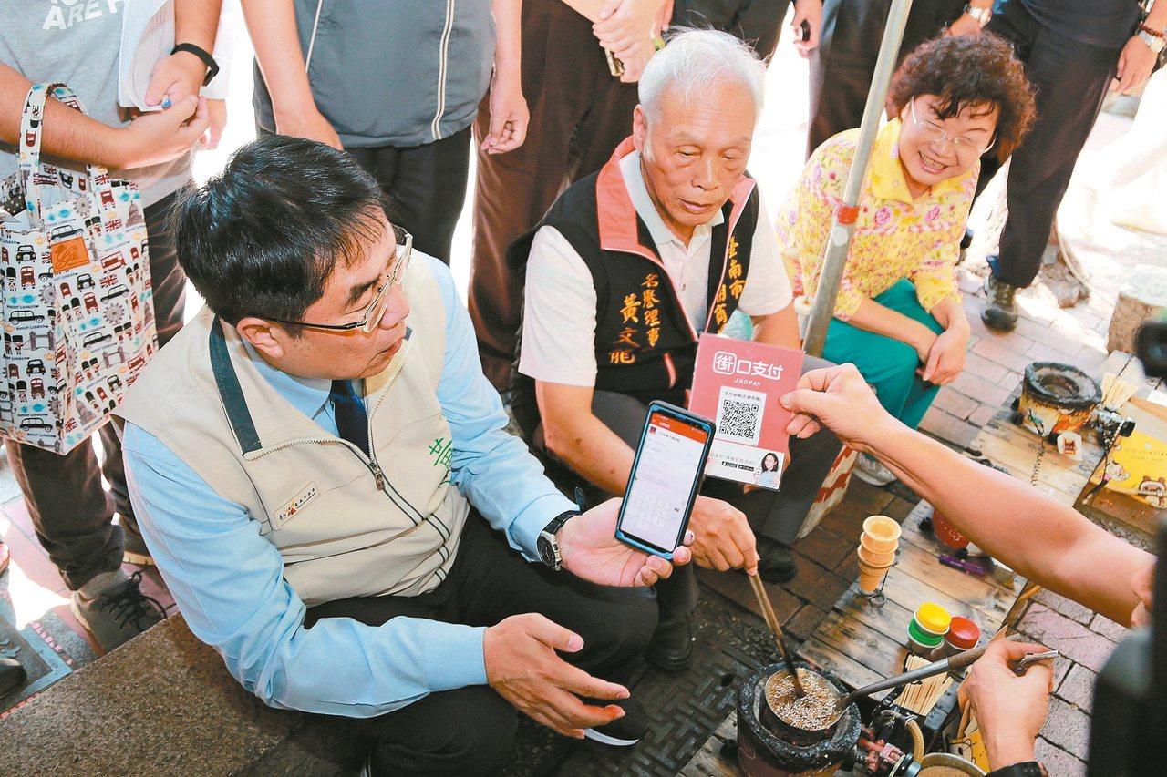 台南市府中街行動支付示範街道昨天揭幕,市長黃偉哲(左)參觀攤商。 圖/市政府提供