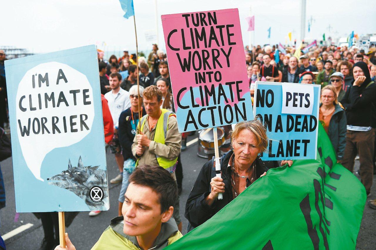 英國民眾廿二日在反對黨工黨於布萊頓舉行年會時在場外示威,要求政黨更重視氣候變遷問...