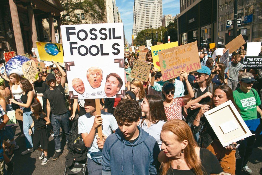 紐約年輕人20日參加氣候罷課抗議活動,要求世界領袖解決暖化問題(見圖)。 美聯社
