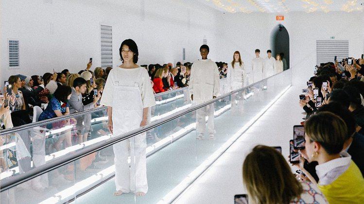 模特兒們在轉換成日光燈的會場中被綠色輸送帶運送出來,他們清一色穿著帶點混濁感的白...
