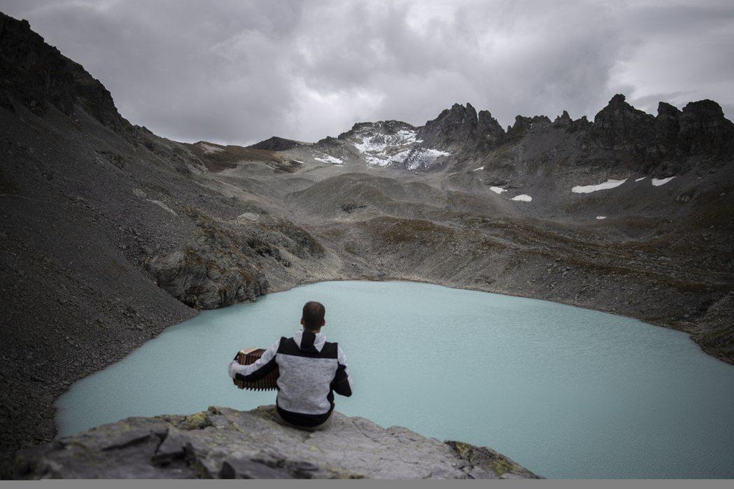 環保人士22日為垂死的瑞士Pizol冰河舉行喪禮,一名登山客在一旁拉手風琴。美聯...