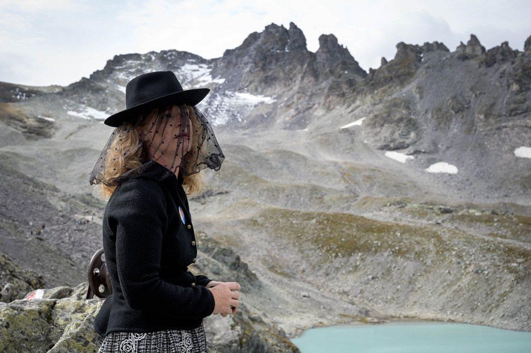 瑞士一名女子22日身穿喪服,參加比索爾冰川的「送葬」行列。冰川專家指出,比索爾冰...