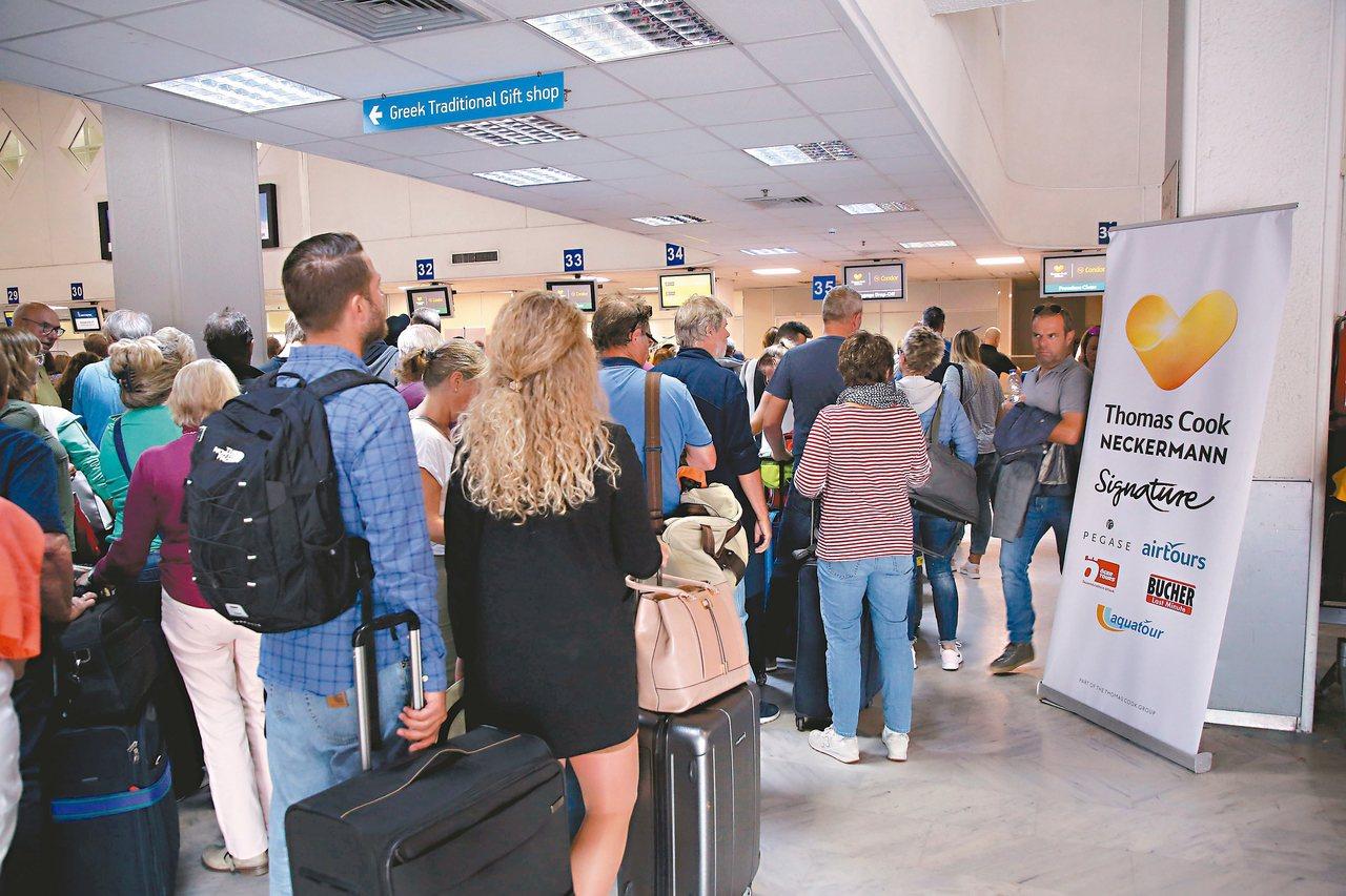 民眾廿三日在希臘克里特島機場的湯瑪士庫克旅行社櫃台前排隊,打聽回國班機消息。 (...