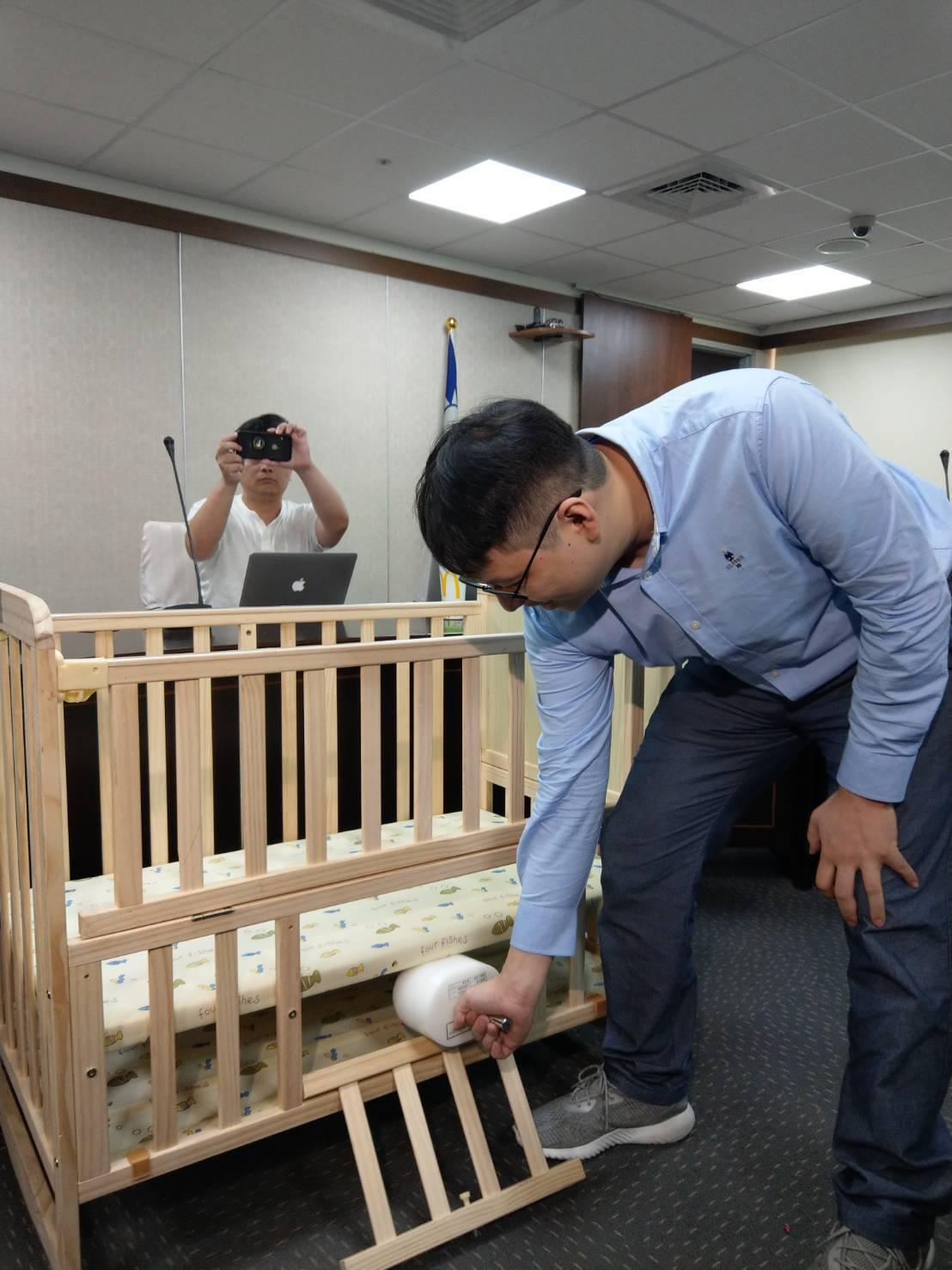 標檢局人員示範檢測嬰兒床,內部之孔洞、縫隙及開口大小若不符合規定,可能會夾到手指...