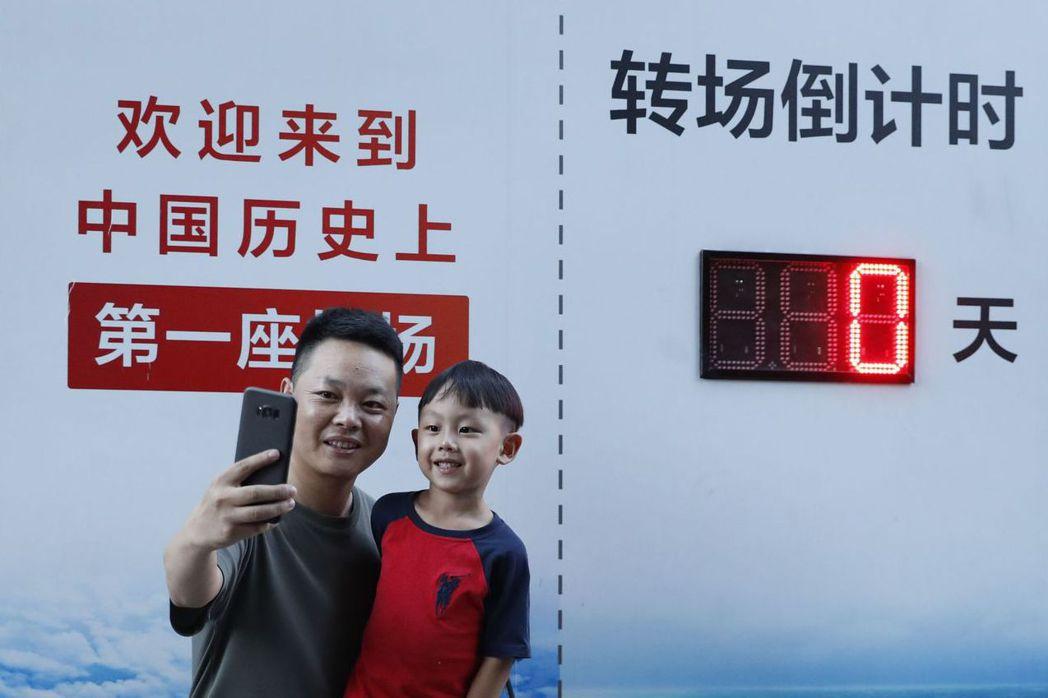 9月25日,市民在南苑機場轉場倒計時牌前自拍。 (中新社)