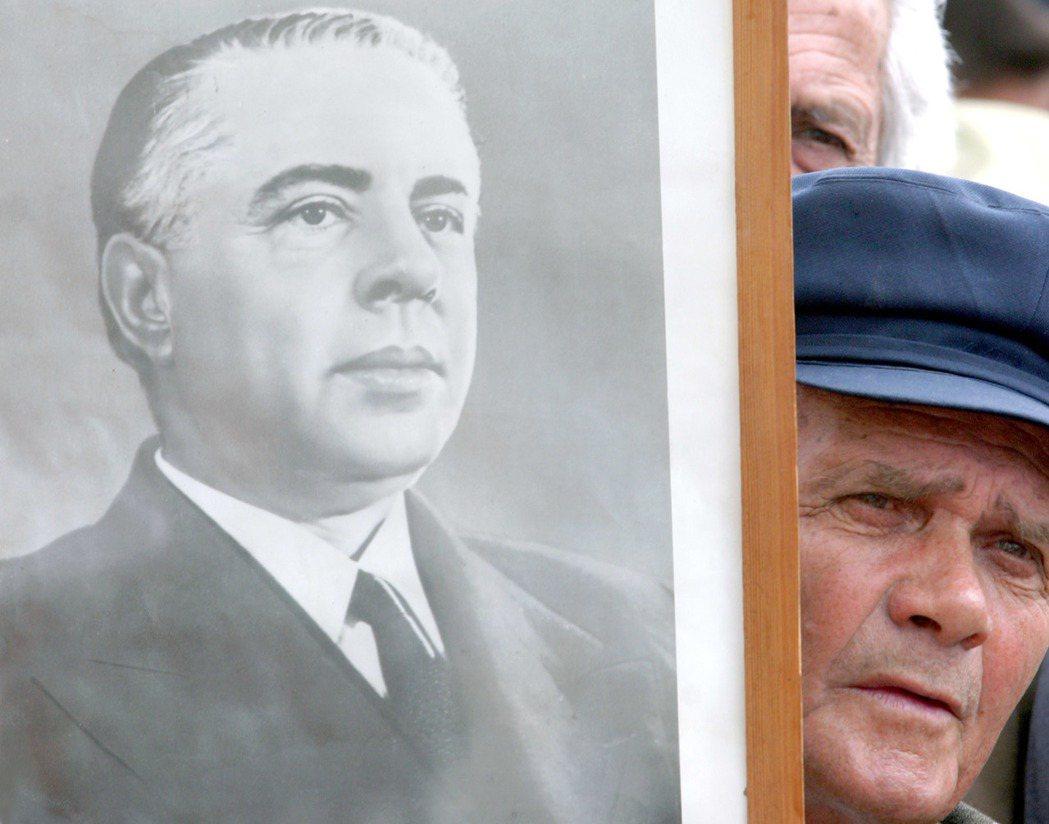 阿爾巴尼亞一名男性拿著已故獨裁者霍查的肖像。(路透)