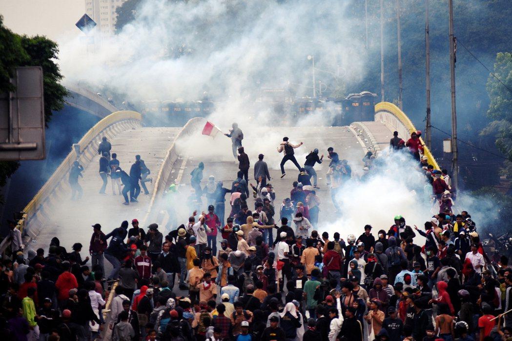 圖為25日示威過程中警方向雅加達示威者發射多發催淚彈。印尼首都雅加達自23日有數...