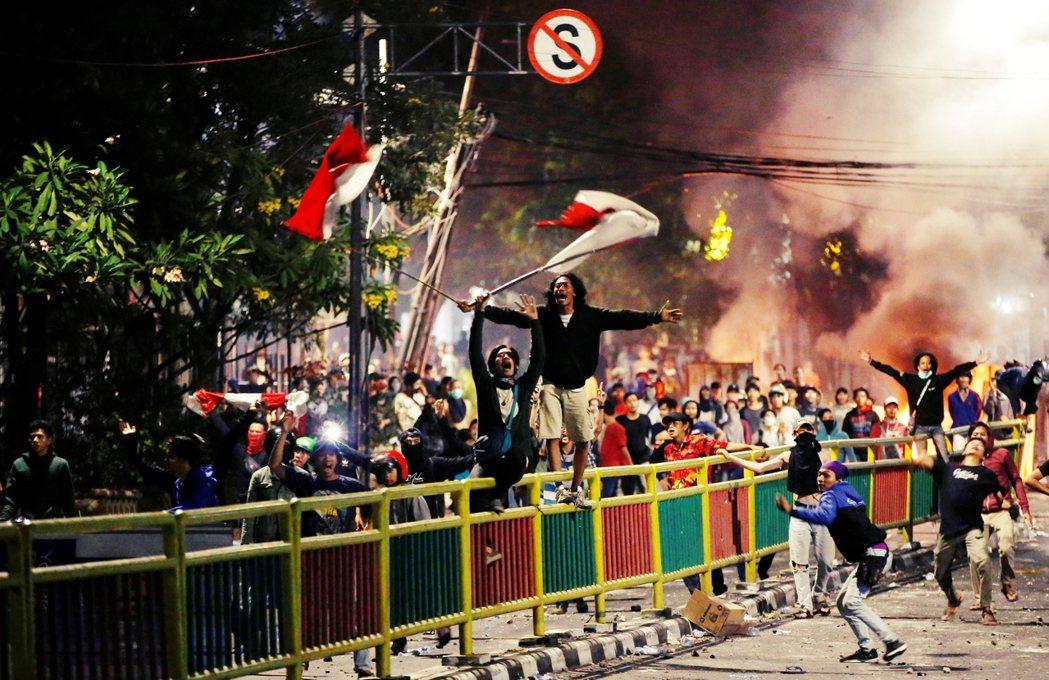示威學生在街上揮舞著印尼國旗。以歐美為主的國際媒體在報導標題上,多聚焦其中的針對...