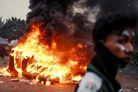 雅加達街頭上,示威者與警察的互動越趨緊張,圖為路上被焚燒的車輛。 圖/路透社