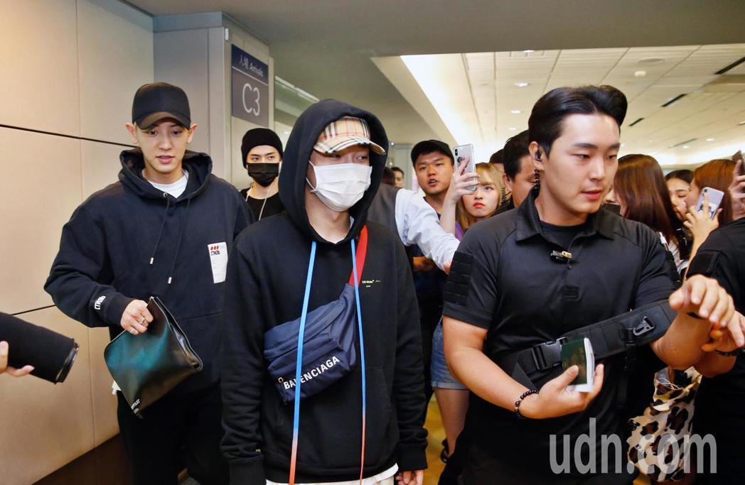 韓團EXO下午搭機抵台,約有百位粉絲在機場管制區內接機,粉絲們拿著手機搶拍偶像。...