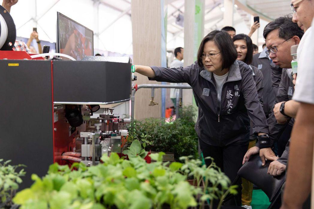 總統蔡英文視訪「創新農機館」,體驗由國內產學共同研發的軟夾式蔬果種苗嫁接機。 光...