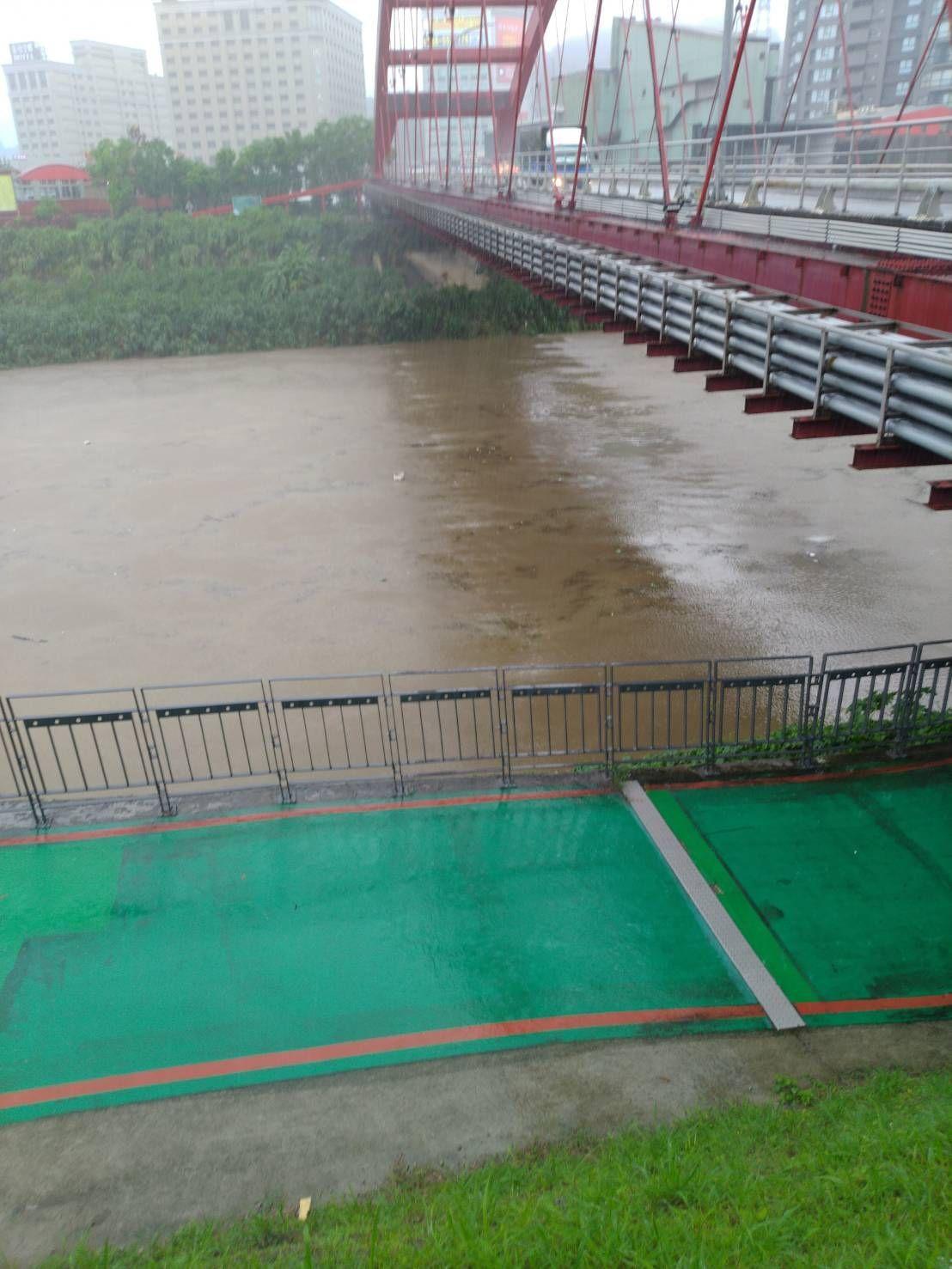 汐止南陽橋下水面因豪雨升高,水位幾乎快跟自行車道一樣高。圖/汐止偵水志工提供