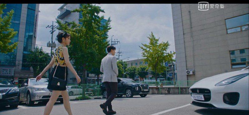 IU在韓劇「德魯納酒店」中選穿VERSACE小洋裝,搭配LONGCHAMP Cavalcade黑色帶鍊皮夾包。圖/擷取自愛奇藝台灣站