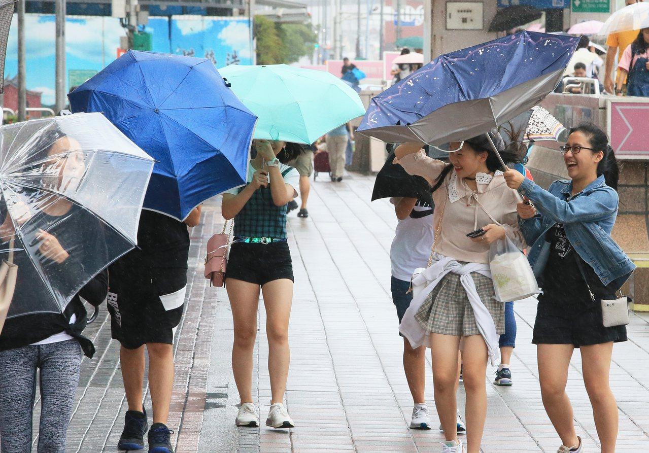颱風米塔持續逼近台灣,台北今天下午出現間歇性風雨,有的路人雨傘開花。記者潘俊宏/...