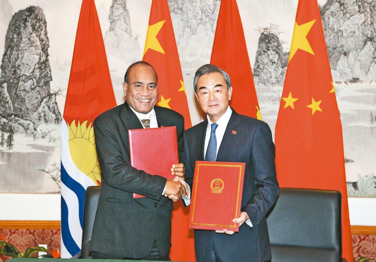 中國大陸外長王毅(右)27日在紐約與吉里巴斯總統兼外長馬茂簽署復交聯合公報。 新...