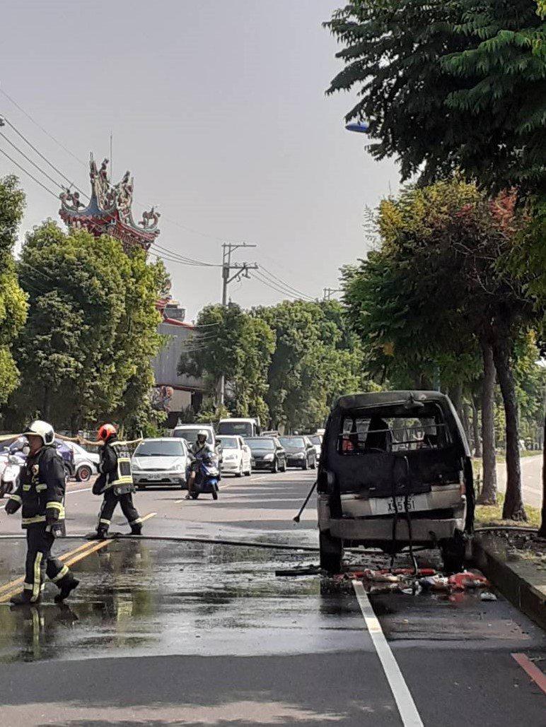 台中市大里區立元路的水防道路上一輛廂型車昨上午突然起火,疑是後後車廂放了打火機及泡棉,因高溫引起自燃。圖/民眾提供