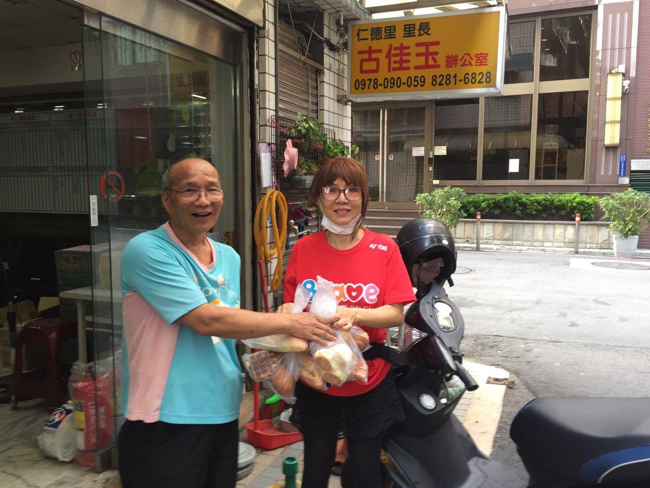 新北讓愛走動關懷協會理事長邱大信(左)拿食物銀行的麵包給里長,再贈給社區的弱勢家...