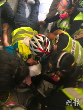 有一名身穿記者反光衣的女記者眼部中彈受傷,現場的急救員表示為橡膠子彈,正為傷者搶...