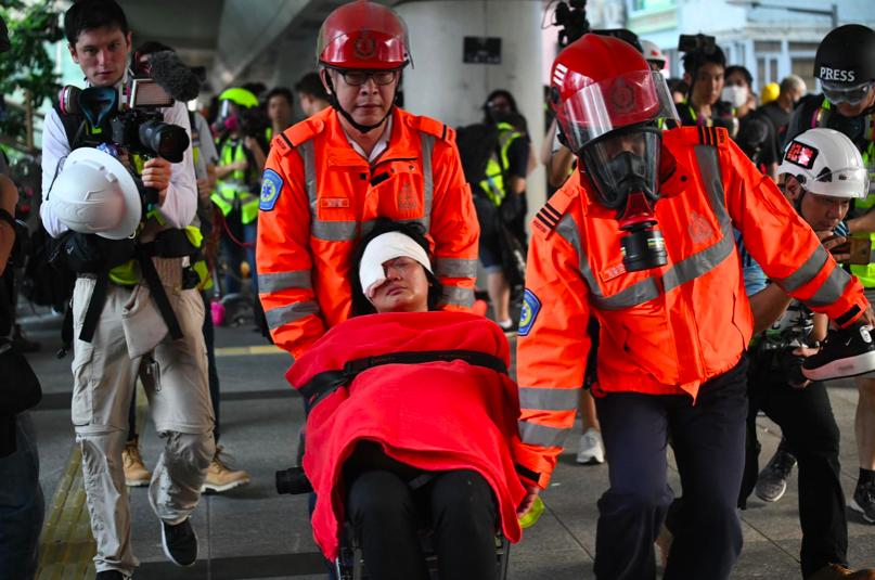 印尼女記者右眼被港警塑膠子彈打中,急救員到場,將該名女子抬到擔架床上送上救護車離...