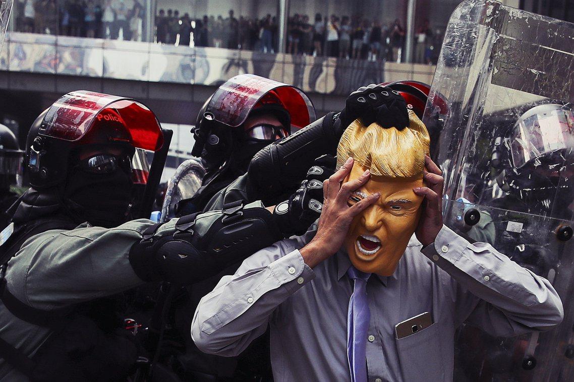 照片中頭戴川普面具的遭補男子,據港媒證實,即為香港知名社運份子楊繼昌。一名戴著川...