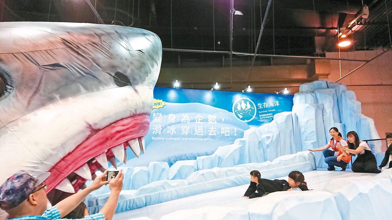 「變變變!MOVE生物體驗展」中,穿上企鵝裝的小朋友慢慢朝巨大白鯊的嘴裡滑去,驚...