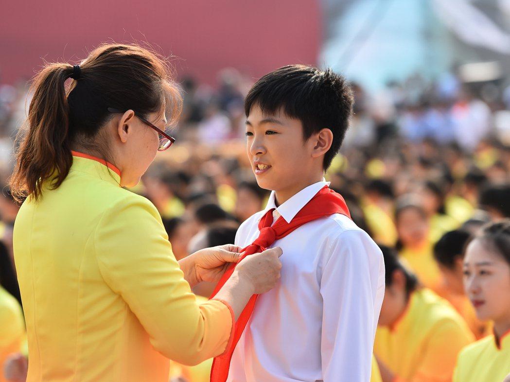 中共在北京天安門廣場慶祝建政70年,一名輔導老師在廣場上為學生整理著裝。  (...