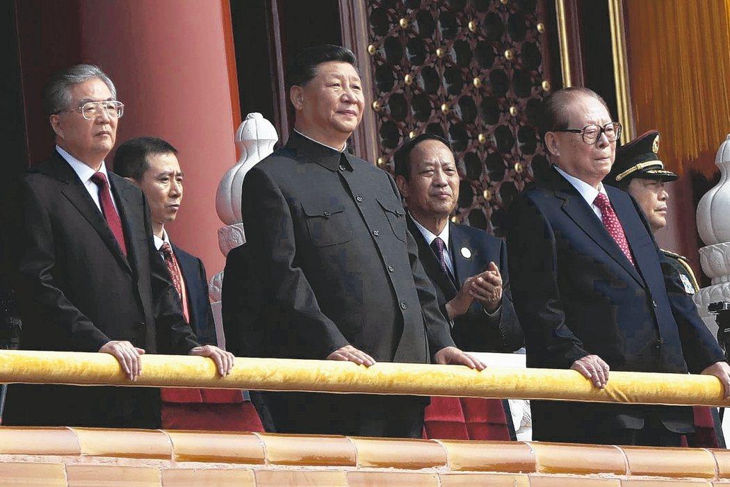 中國國家主席習近平(中)主持建國70周年閱兵,兩邊分別是前國家主席胡錦濤(左)和江澤民(右)。 歐新社