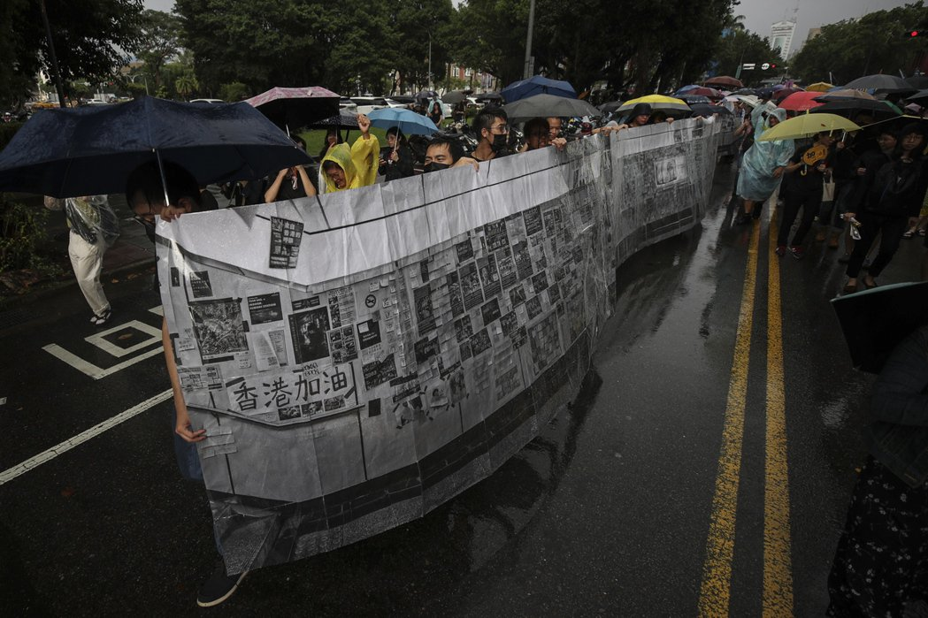 遊行群眾合力舉著六公尺的橫幅照片,重現日前被拆除的公館連儂牆。 圖/歐新社